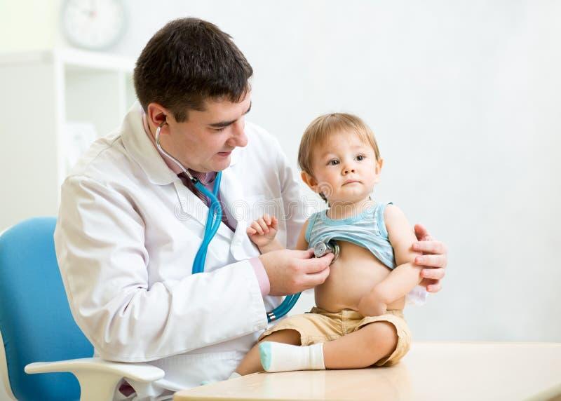 Undersökande hjärtslag för doktor av ungepojken med royaltyfri bild