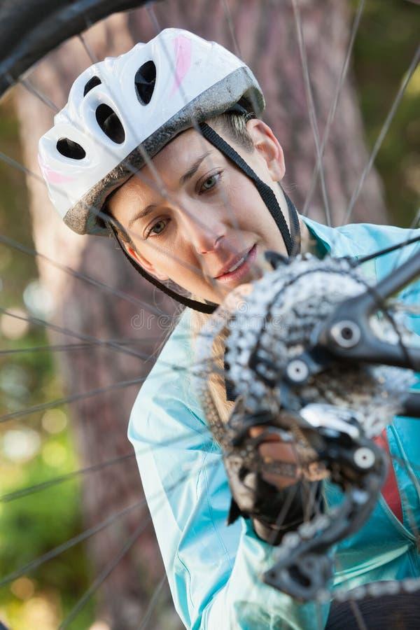 Undersökande hjul för kvinnlig bergcyklist av hennes cykel arkivbild