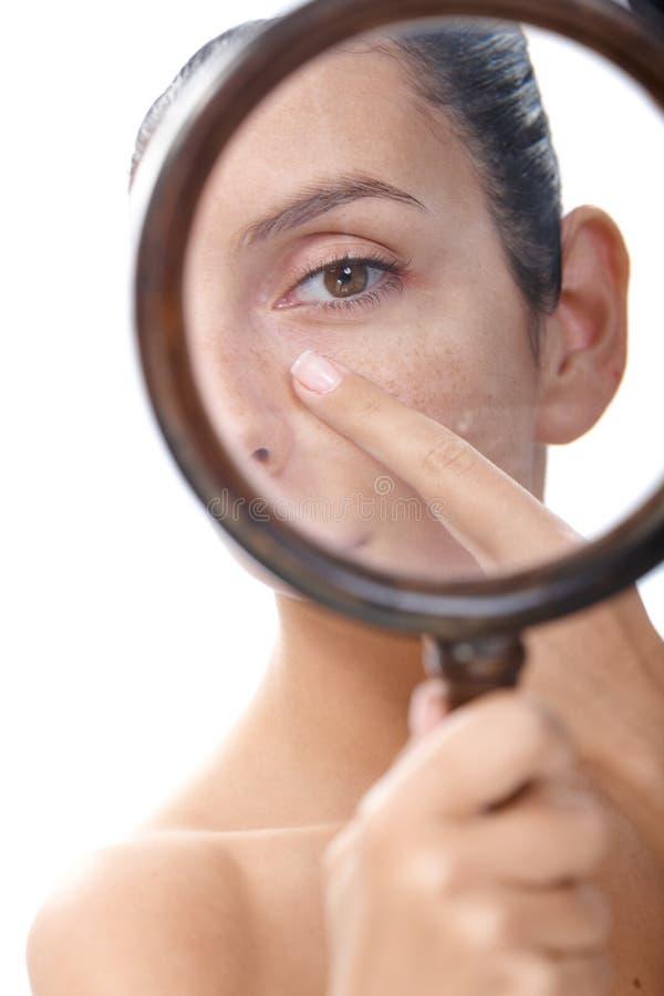 Undersökande hud för ung kvinna med förstoringsapparat royaltyfria foton