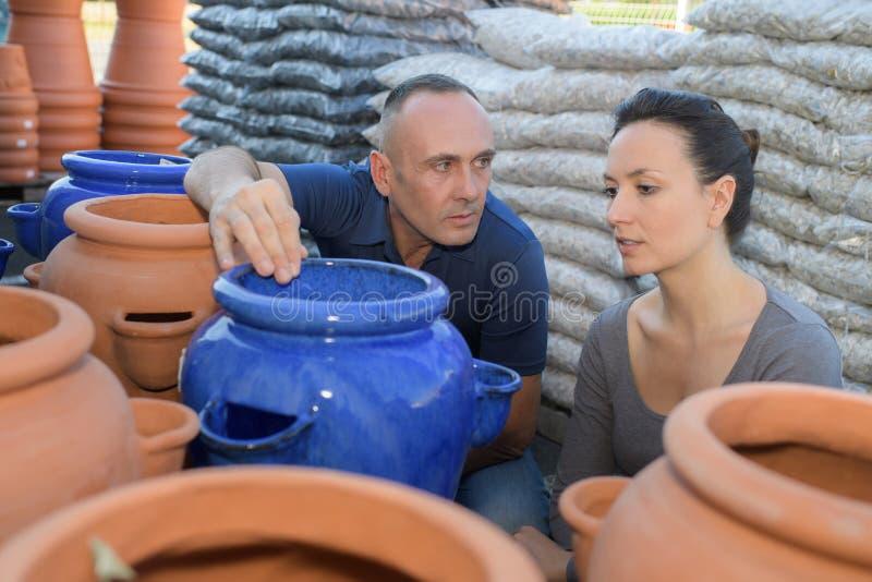 Undersökande kruka för man och för kvinnlig keramiker i krukmakeriseminarium royaltyfri foto