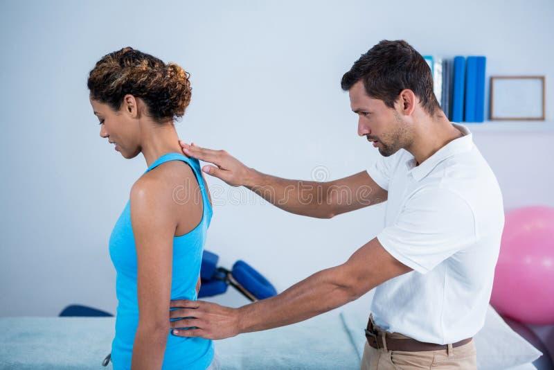 Undersökande kvinnas för fysioterapeut baksida royaltyfri foto