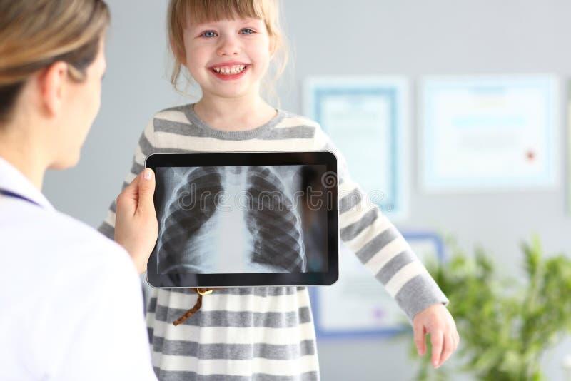 Undersökande liten flicka för kvinnlig doktor med den ultra moderna avläsande minnestavlaPCapparaten fotografering för bildbyråer