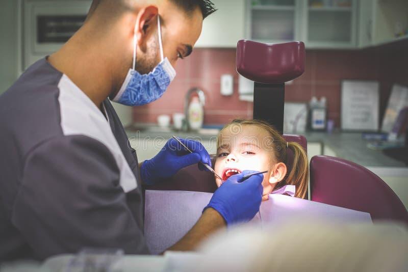 Undersökande liten flicka för ung manlig tandläkare arkivbild