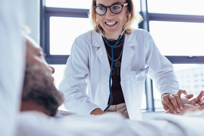 Undersökande manlig patient för kvinnlig doktor i sjukhusrum royaltyfria bilder