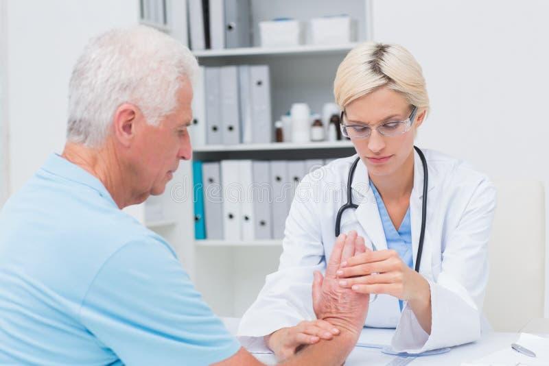 Undersökande manlig patienthandled för kvinnlig fysioterapeut royaltyfri bild