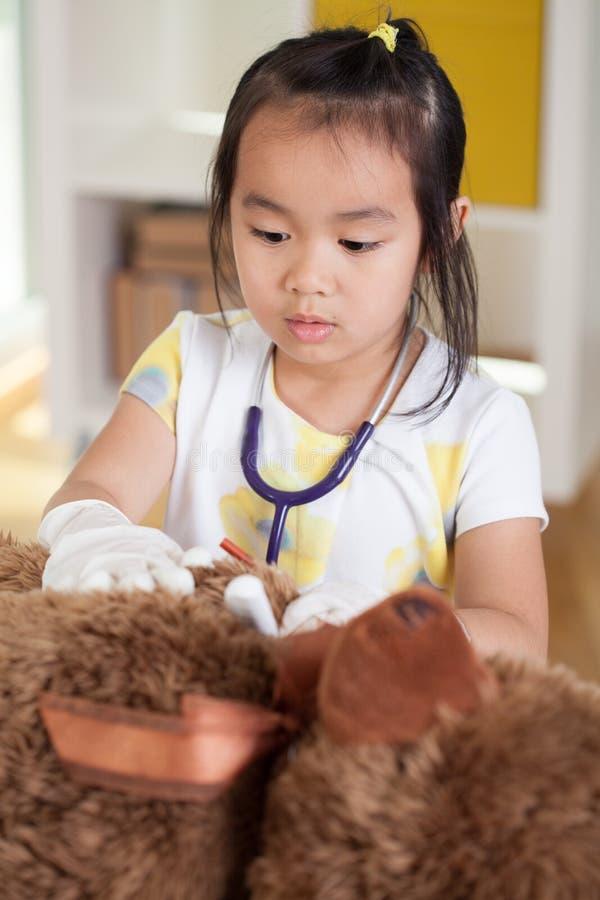 Undersökande nallebjörn för asiatisk flicka fotografering för bildbyråer