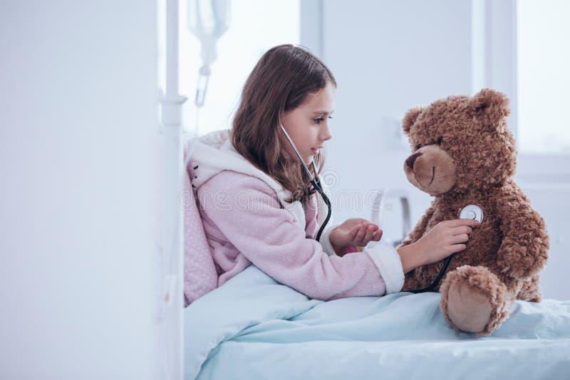 Undersökande nallebjörn för flicka arkivfoto