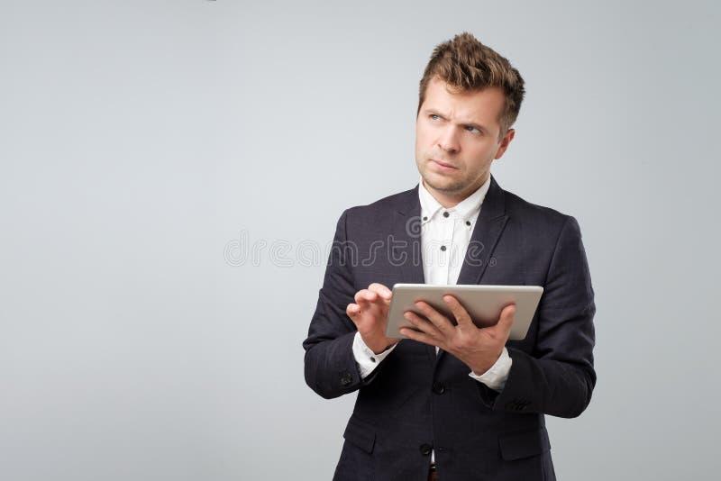 Undersökande ny grej Säker ung stilig man i skjorta och band som arbetar på den digitala minnestavlan royaltyfri foto