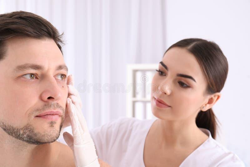 Undersökande patient för doktor i klinik royaltyfria bilder
