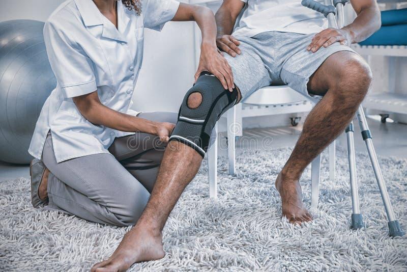 Undersökande patientknä för fysioterapeut arkivbild
