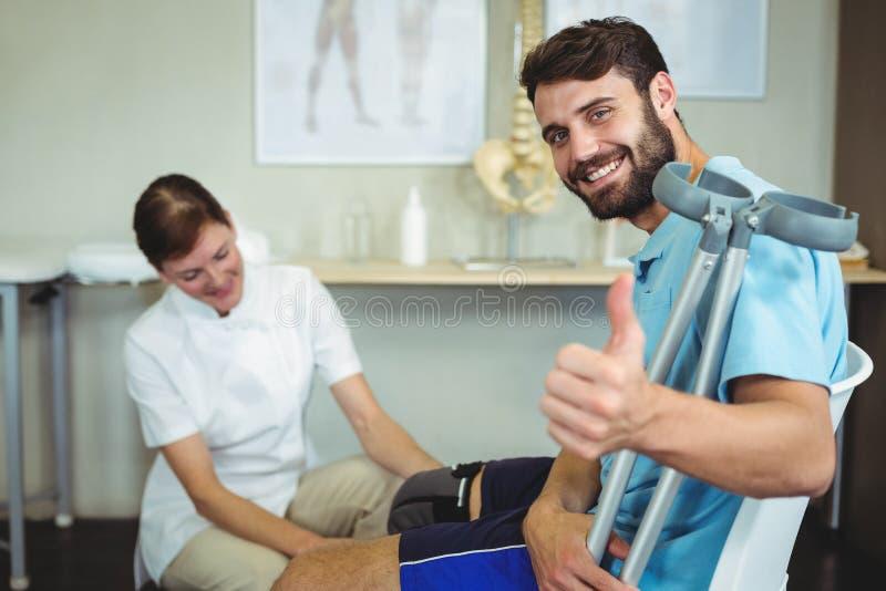 Undersökande patientknä för fysioterapeut royaltyfri foto