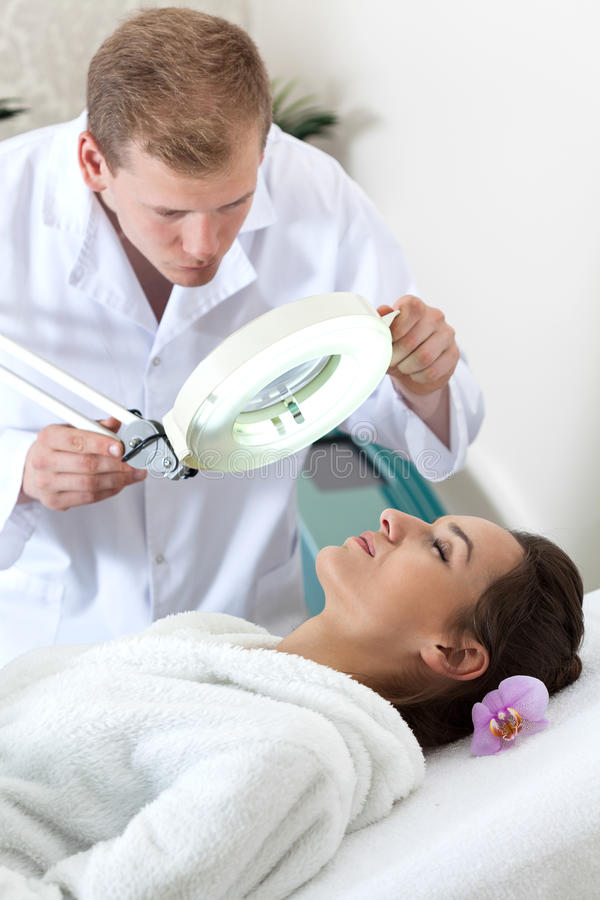 Undersökande patients för Cosmetologist villkor för hud arkivbilder