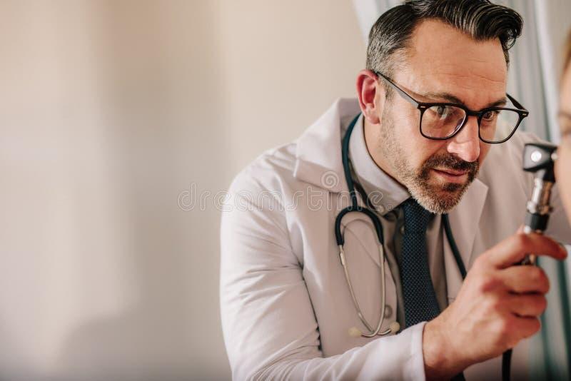 Undersökande patients för manlig doktor öra royaltyfri bild