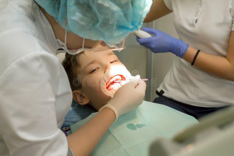 Undersökande pojkemun för Orthodontist royaltyfri bild