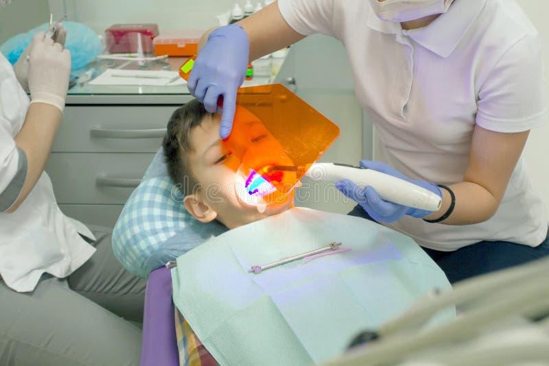Undersökande pojkemun för Orthodontist royaltyfri foto