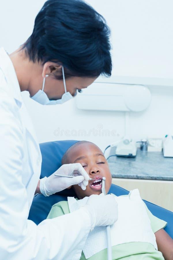 Undersökande pojketänder för kvinnlig tandläkare i tandläkarestol royaltyfria bilder