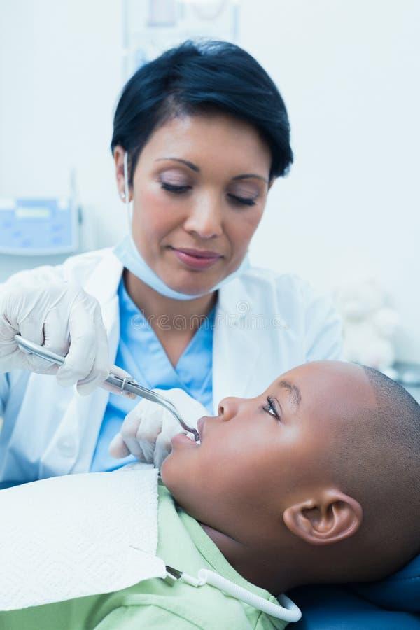 Undersökande pojketänder för kvinnlig tandläkare i tandläkarestol royaltyfri bild