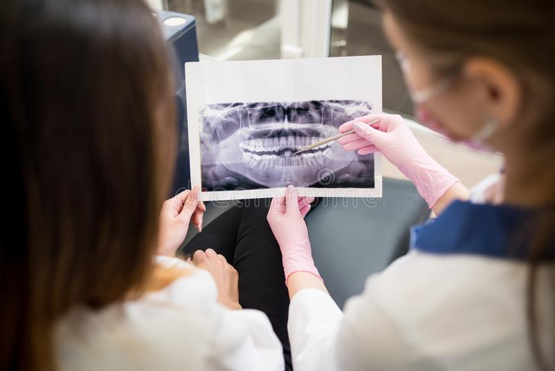 Undersökande röntgenstrålebild för kvinnlig ung tandläkare med den kvinnliga patienten i tand- klinik och förbereda sig för behan arkivfoton