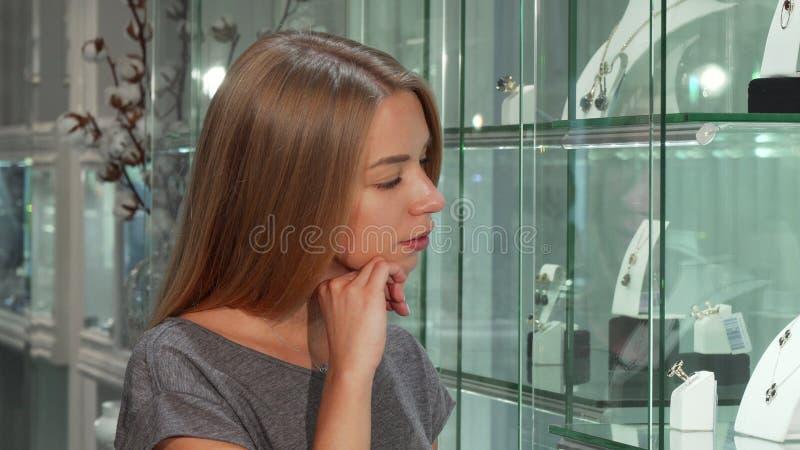 Undersökande skärm för attraktiv ung kvinnlig kund på smyckenlagret arkivfoton