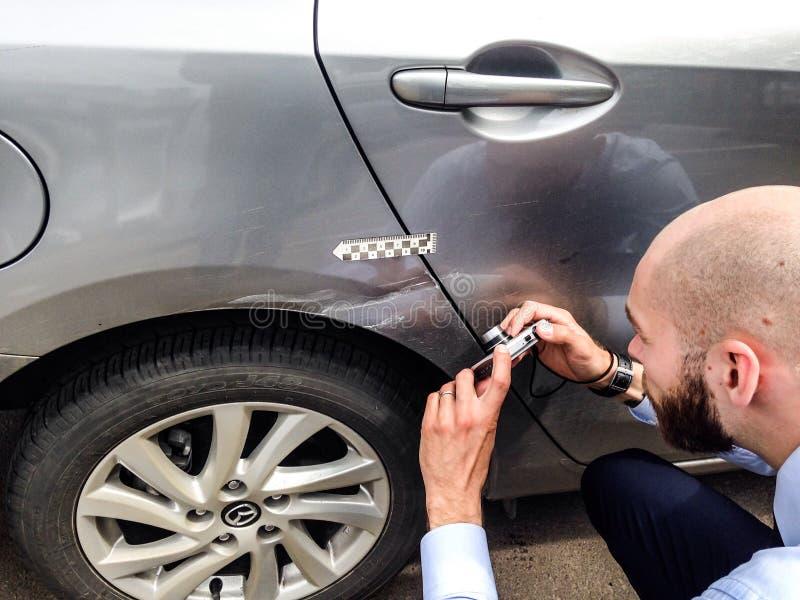 Undersökande skada för försäkringregulator till bilyttersida royaltyfria bilder