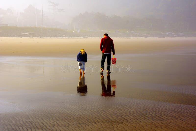Undersökande strand för fader och för dotter på lågvatten arkivfoton