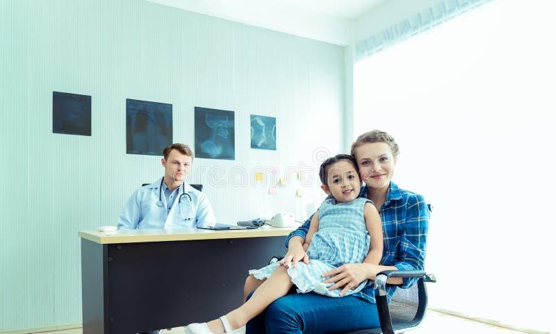Undersöker den pediatriska doktorn för den unga vänliga caucasianen den tålmodiga flickan för barnet med hennes moder, konsu arkivbild