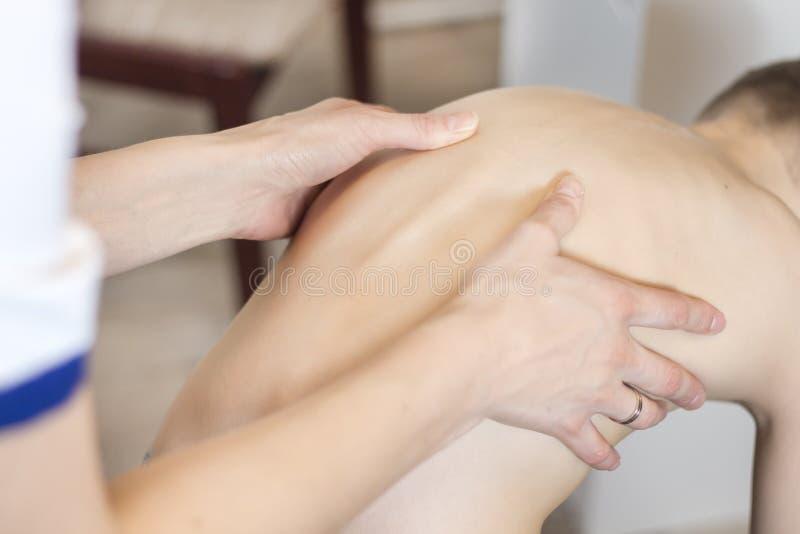 Undersökning av ett barns defekt i ställing Doktorns händer undersöker ryggen av en liten patient royaltyfri foto