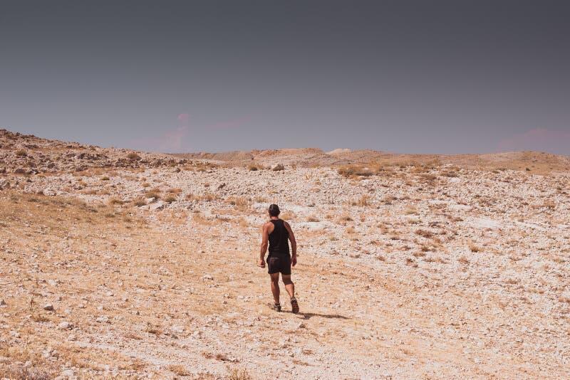 Undersökning - ensam människa som går i begrepp för en stenig ökenfrihet och affärsföretaglivsstil- och sport fotografering för bildbyråer