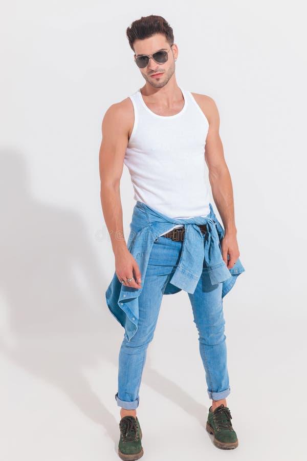 Undershirt вскользь человека нося белые и стойки солнечных очков в spo стоковое изображение rf