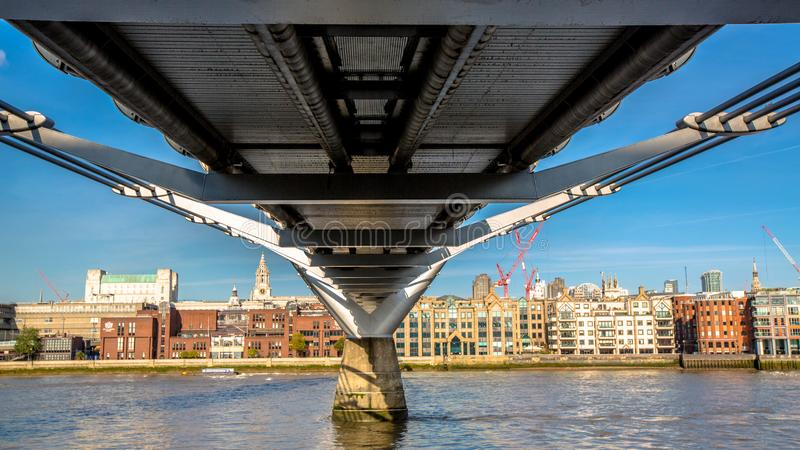 Undersidasikt av milleniumbron som ser in mot staden av London arkivfoto