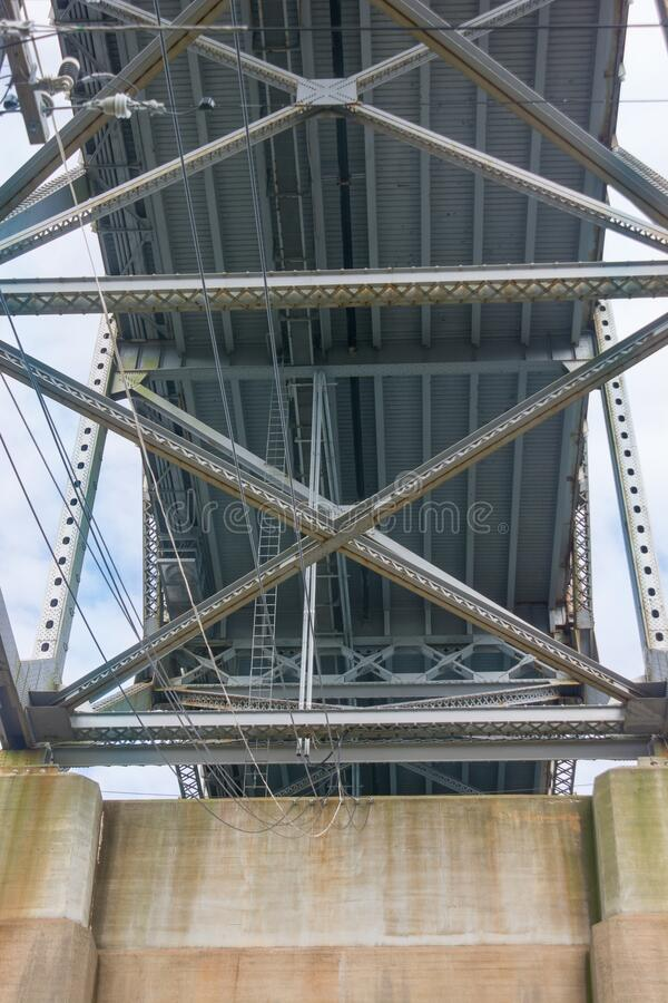 Underside of the Bourne Bridge showing the intricate ironworks and heavy cement footings. Silver iron work and cement pier supporting the underside of the Bourne stock images