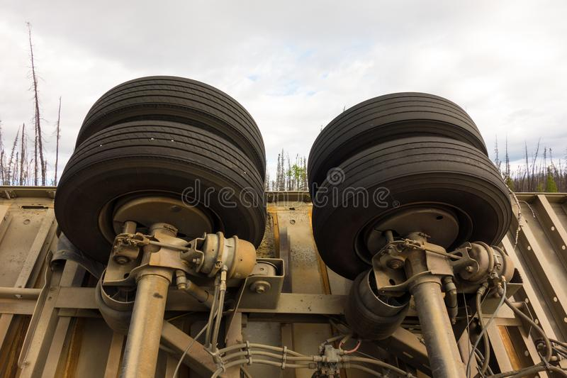 The underside of a crashed trailer in a remote part of british columbia. The wheels of a trailer at an accident scene along the challenging cassiar highway in royalty free stock photos