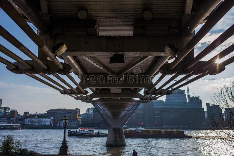Underside of Millennium Bridge over River Thames, London, England royalty free stock photography