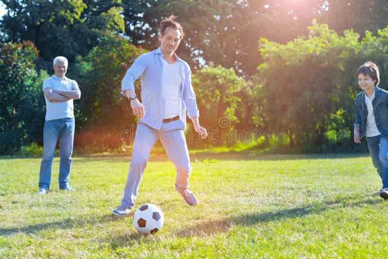 Understöd familj som spelar fotboll tillsammans fotografering för bildbyråer