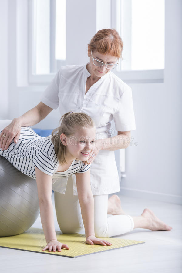 Understödjande flicka för fysioterapeut med scoliosis arkivfoton