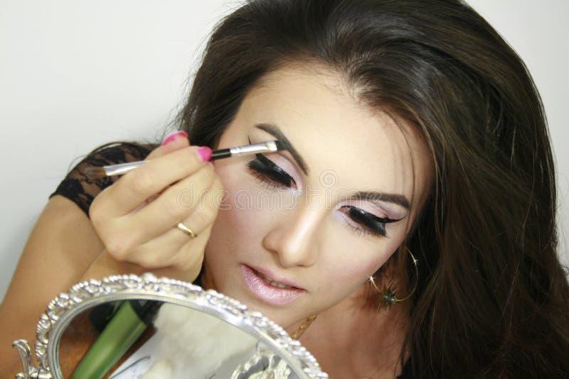 Understryker den härliga flickan för makeup hennes ögonbryn, ger en blick på dig, underbar makeup, spegel för prydnadrenässanssil royaltyfria foton