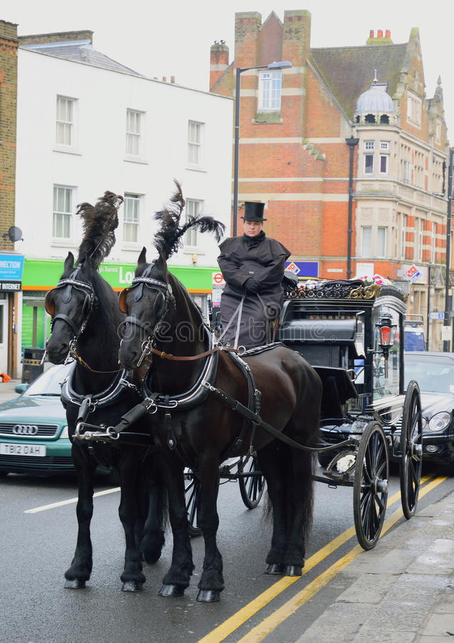 UNDERTAKER. With Victorian era horse-drawn hearse on the street in High Barnet, London stock photo
