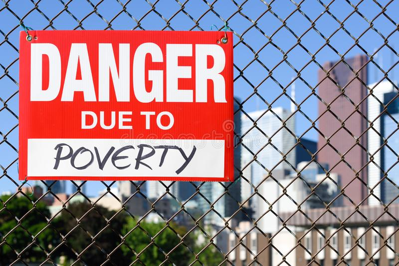 Underteckna armod för fara som tack vare hänger på staketet fotografering för bildbyråer