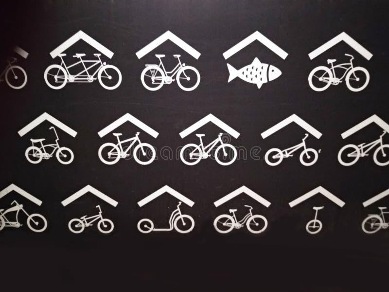 Underteckna in svart bakgrund med vita teckningar stiliserad symbolisk framställning av hollanden ny fisk och cyklar royaltyfri foto