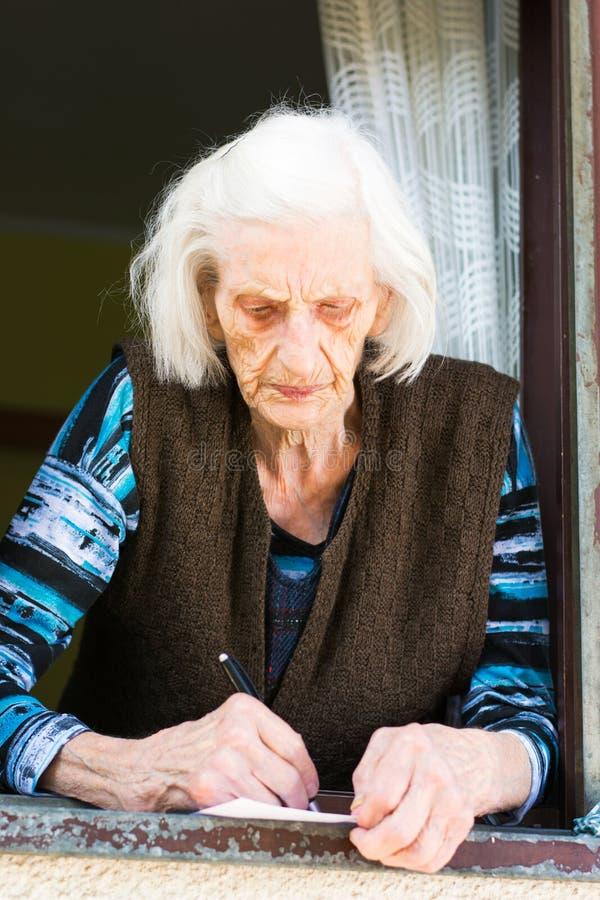 Undertecknande avgångkontroll för hög kvinna hemma royaltyfri foto
