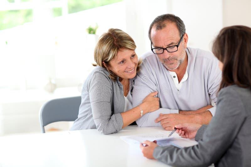 Undertecknande avtal för höga par med fastighetsmäklaren royaltyfri fotografi