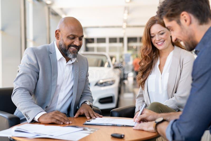 Undertecknande avtal för man som köper den nya bilen royaltyfria foton