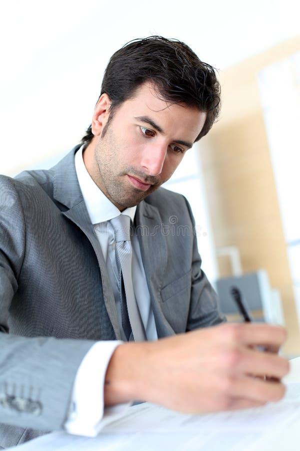 Undertecknande avtal för ung affärsman royaltyfri foto