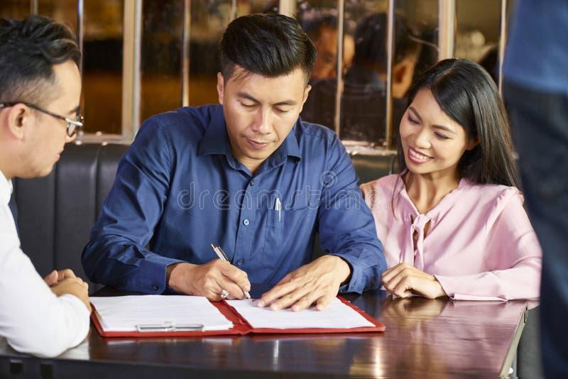 Undertecknande avtal med fastighetsmäklaren fotografering för bildbyråer
