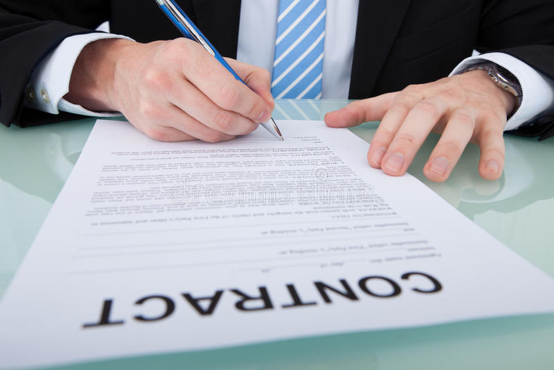 Undertecknande avtalspapper för affärsman på kontorsskrivbordet royaltyfri fotografi