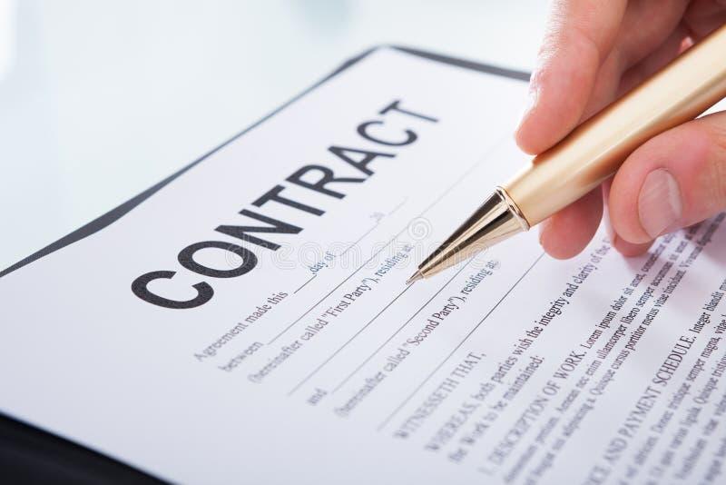 Undertecknande avtalspapper för affärsman på skrivbordet royaltyfri bild