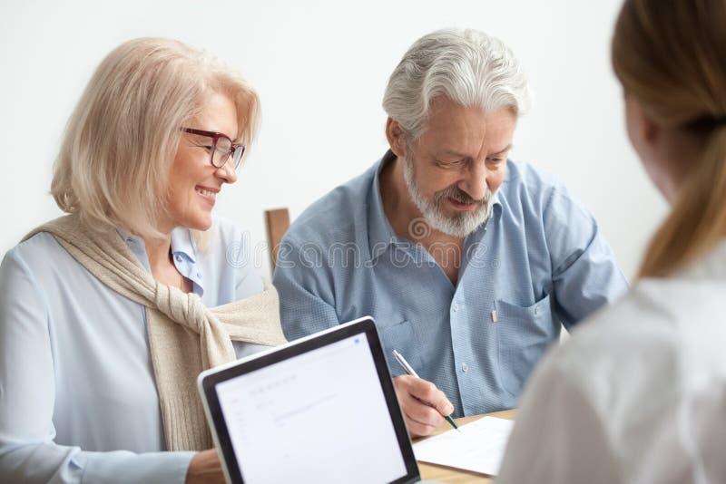 Undertecknande dokument för lyckliga höga par på mötet med finansiellt a arkivfoto