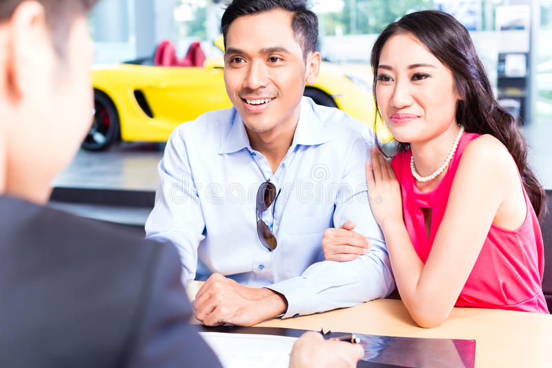 Undertecknande försäljningsavtal för asiatiska par för bil på återförsäljaren royaltyfria foton