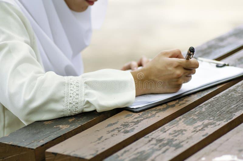 Undertecknande form för ung kvinna som sitter på trätabellen royaltyfria foton