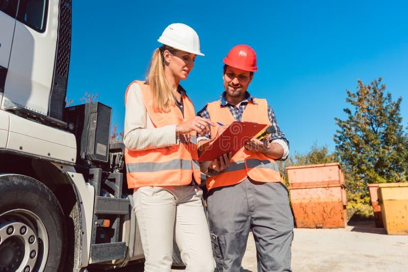 Undertecknande legitimationshandlingar för arbetare som har den levererade rivningspillrorbehållaren arkivfoto